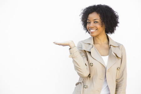 smiling african american woman holding hand up against a white  photo