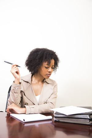 working woman: young african american woman working at desk Stock Photo
