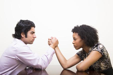 책상에 민족적인 젊은 비즈니스 남자와 여자 팔 씨름