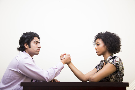 office politics: ethnic young business man and woman arm wrestle on desk