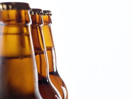 Upper part of three beer bottles isolated over white background photo