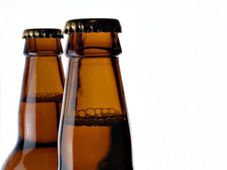 Upper part of two beer bottles isolated over a white background photo