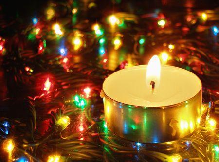 Candlelight and  colorful christmas garland lights photo