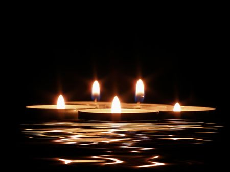 Candles and its reflection in dark water photo