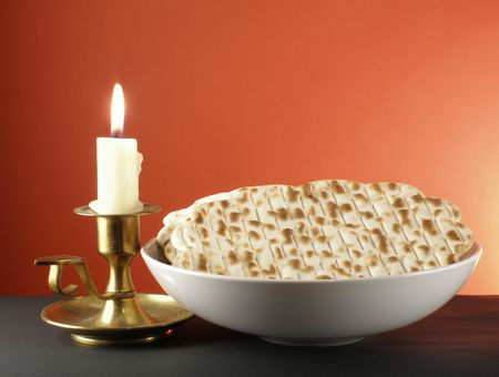 plateful: Candle and a plateful of matzoh - jewish passover bread