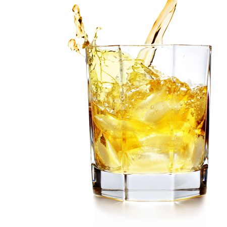 nightcap: Whiskey pouring into glass over white background Stock Photo
