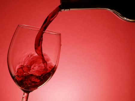 Red wine pouring into the glass over red background