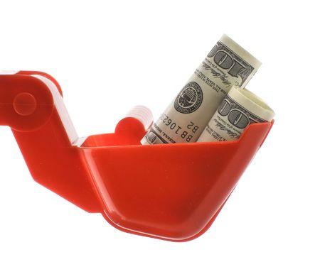 honorarium: Dollars bills within toy excavator bucket isolated over white background Stock Photo