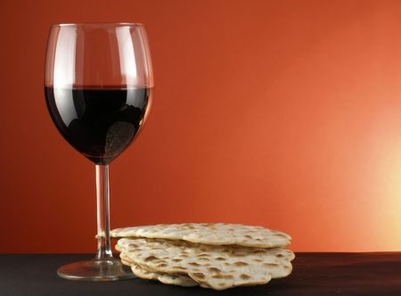 seder: Glass of wine and matzoh over red background   Stock Photo