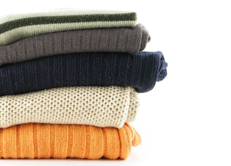 Folded woolen sweaters isolated over a white background photo