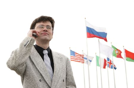 Businessman with cellular phone and flags in the background photo