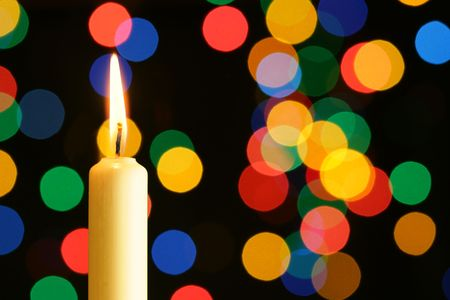 Candle with flame over colorful lights background photo