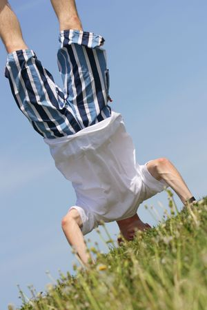 antipode: Man stand upside down against a blue sky