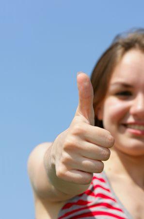 beatitude: Teen girl show thumbs up sign against a blue sky Stock Photo