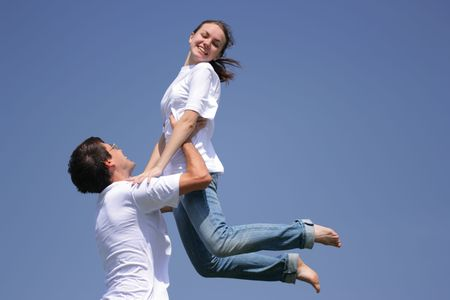 beatitude: Beautiful young girl and young man have fun against bluee sky