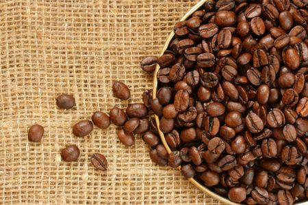 colombian food: Plate of coffee beans close-up over burlap