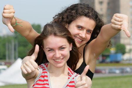 Two teen girls show thumbs up signs photo