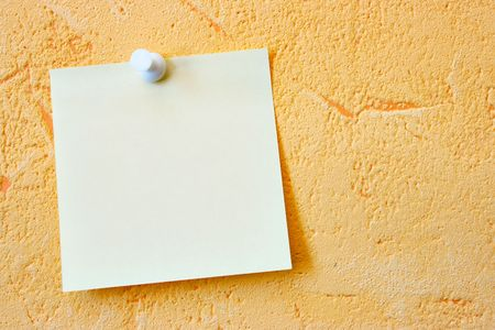 Single blank note paper attached to a wall