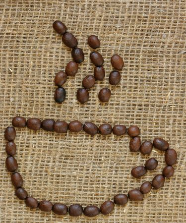Outline of coffee cup made from coffee beans over burlap background photo
