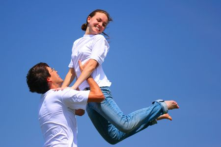merriment: Beautiful young girl and young man have fun against bluee sky
