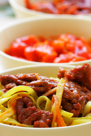 plateful: Chinese noodles and fried beef within bowl close-up Stock Photo