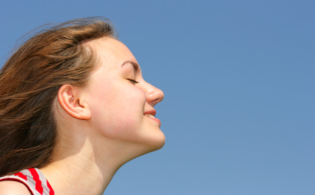 blessedness: Profile of young pretty girl over blue sky background