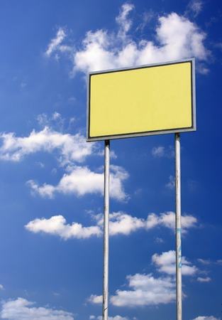 Small blank sign against deep blue sky background photo