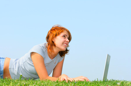 Young woman working with notebook on the grass