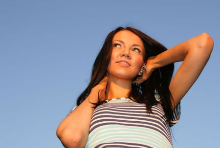 beatitude: Young happy woman against blue sky at evening light