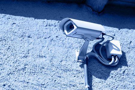 mounted: Security camera gemonteerd op de stenen muur afgezwakt in blauw  Stockfoto