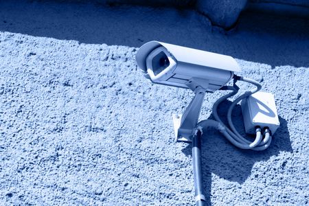 Security camera mounted on stone wall toned in blue photo