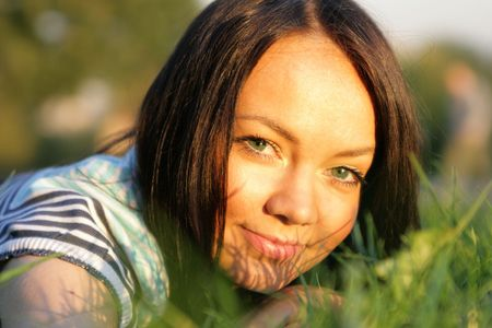beatitude: Young happy woman lie on the grass at evenings