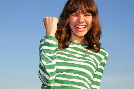 Teen girl show gesture against a blue sky photo