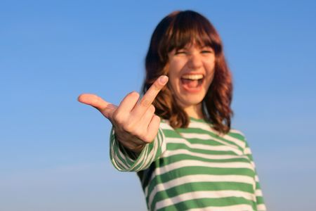 Young girl show gesture against blue sky photo