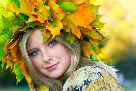 Miss Autumn. Beautiful blue-eyed woman with diadem made from yellow maple leaves photo