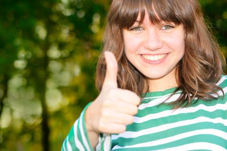 Teen girl show thumb up sign with copyspace on left. Shallow DOF, focus on the eyes photo