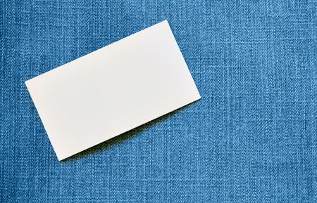 Blank visiting card over blue jeans background photo