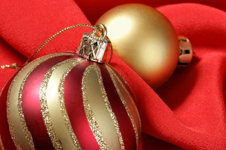 folds: Christmas balls over red silk background. Focus on the stripy ball. Stock Photo