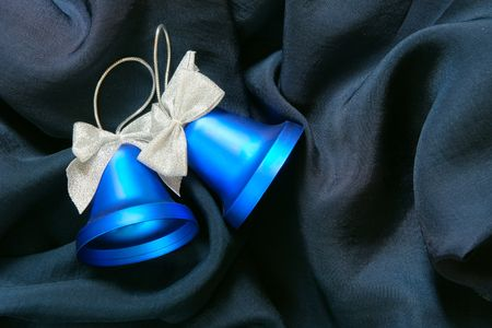 bedeck: Two Christmas bells over dark blue fabric background