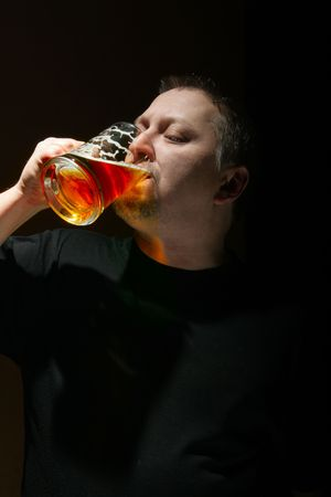 Man drinking beer over black background with space for your own text below photo