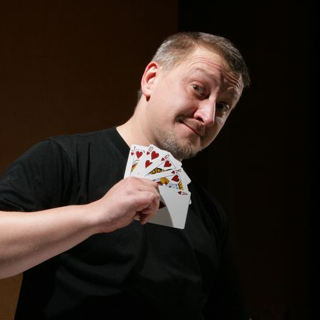 Portrait of the man with royal flush over dark background  photo