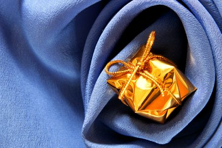 Expensive gift over blue silk background with folds photo