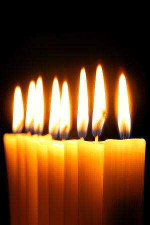 judaica: Eight burning candles over black background Stock Photo