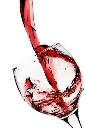 Red wine pour into glass close-up isolated over white background photo