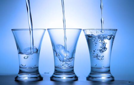 Clear liquid pour into three wineglasses toned in blue color Stock Photo - 2357795