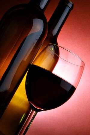 Still-life with two bottles and glass of red wine over red background photo