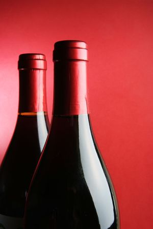 Two corked wine bottles over red background photo