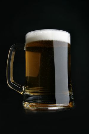 Dark beer with froth over black background photo