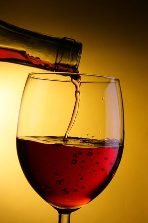 bocal: Red wine pour into glass close-up over yellow background Stock Photo