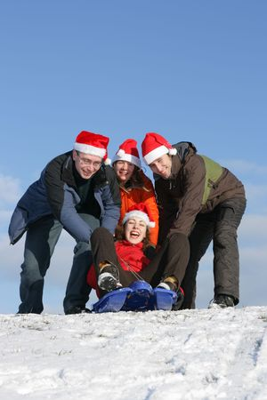 Friends with Santa hats to toboggan in winter Stock Photo - 2481862